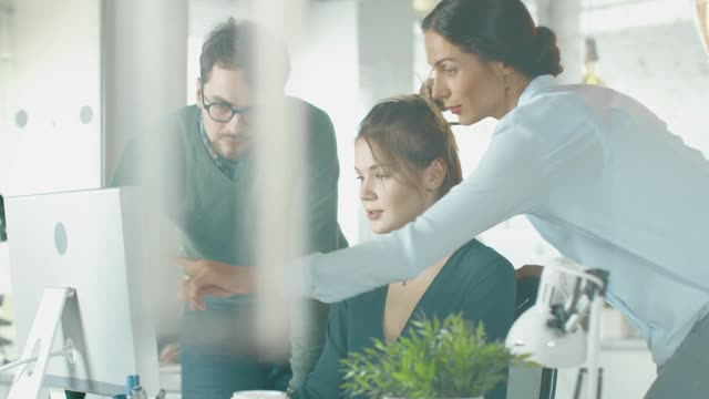 young man and two women stand before computer desk in a creative office they discuss business issues people working in background hn9nv1dne thumbnail medium01 - Payroll & Auto-enrolment